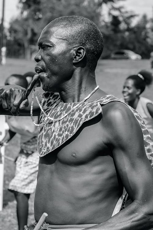 Black and white side view of old African American man in traditional clothes during local party