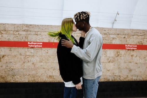Man and Woman Kissing Near White Wall