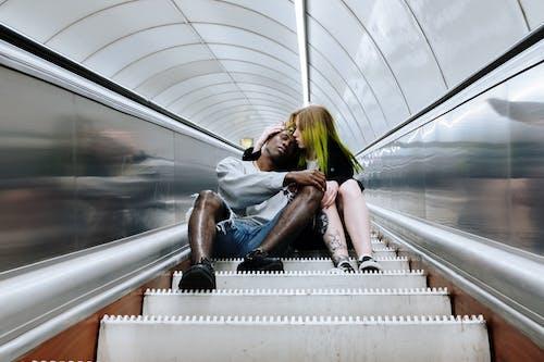 Woman in Black Tank Top and Blue Denim Shorts Sitting on Escalator
