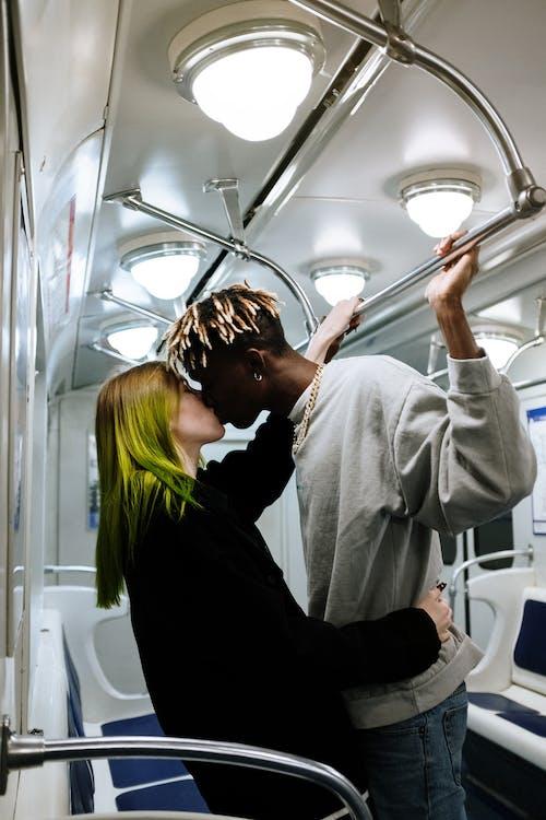 Man in Gray Hoodie Kissing Woman in Black Long Sleeve Shirt