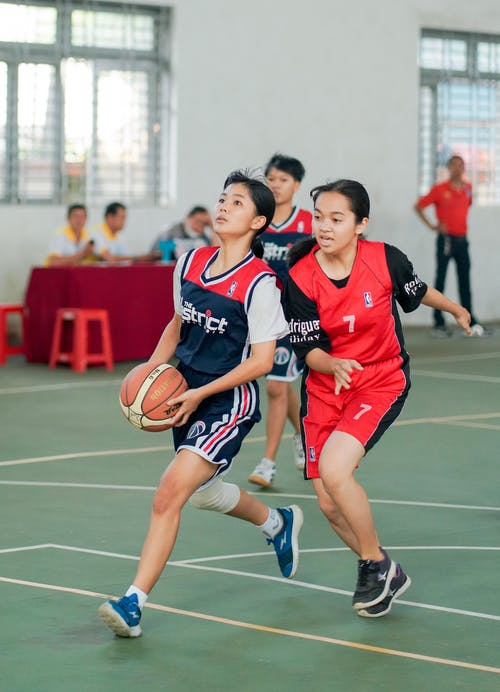 Full body of Asian women team in uniform playing basketball game in hall