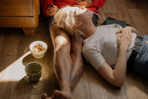 Woman in White T-shirt Lying on Floor