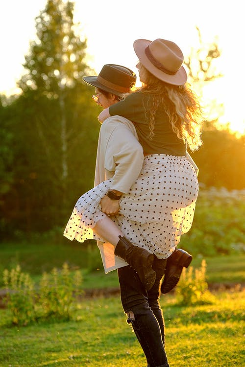 Happy young guy carrying girlfriend on back during romantic date in nature