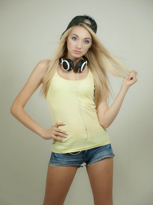 Woman in Yellow Tank Top Wearing Black Fittedcap