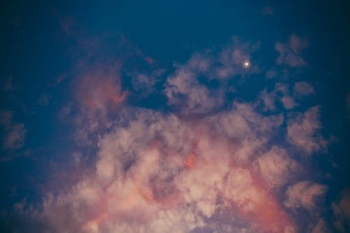 Picturesque view of light pink clouds and small solitude glowing star in vivid dark blue evening sky at sunset