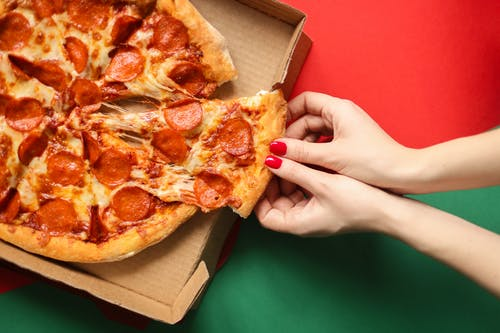 Person Holding Brown and Red Pizza