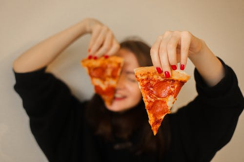 Person Holding Sliced Pizza With Cheese