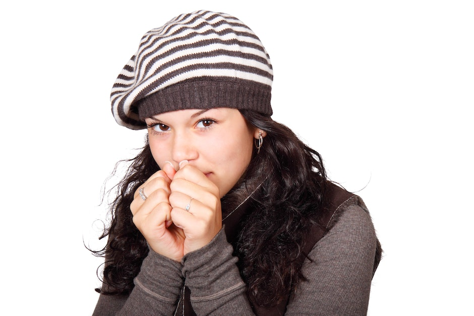 Woman in White and Black Stripe Cap and Grey Shirt Hands to Face