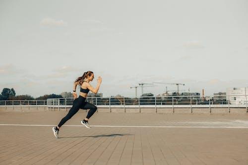 Woman in Black Tank Top and Black Pants Jumping on Brown Wooden Floor