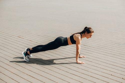 Woman in Black Tank Top and Black Leggings Doing Yoga on Brown Wooden Floor