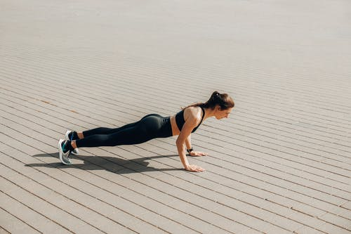 Woman in Black Tank Top and Black Leggings Doing Yoga on Gray Wooden Dock