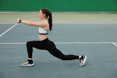 Woman in White Sports Bra and Black Leggings Doing Yoga