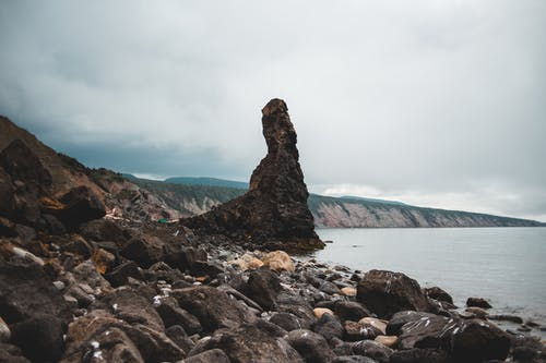 Picturesque scenery of rough rocky cliffs with uneven surface and rough boulders near ocean water in overcast weather
