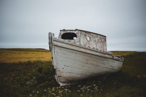 Old boat on grassy field in overcast