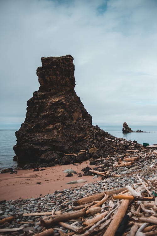 Bristly rocky formation on sea shore under cloudy sky