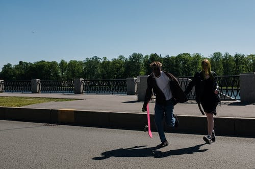 Woman in Black Jacket and Pink Pants Walking on Gray Concrete Pathway