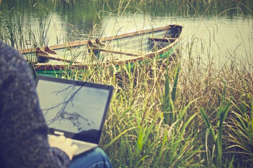 Person Using Black Laptop Computer Near Green Boat