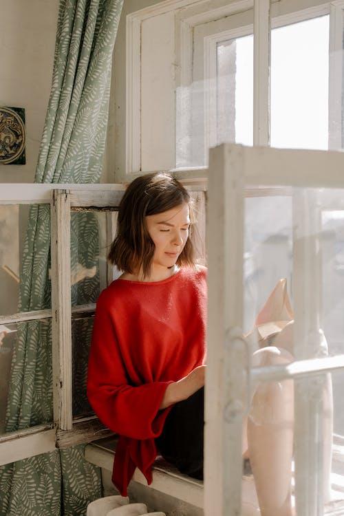 Girl in Red Crew Neck T-shirt Standing Beside White Wooden Framed Glass Window