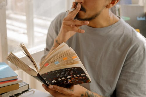 Man in Gray Crew Neck Shirt Holding White and Brown Book