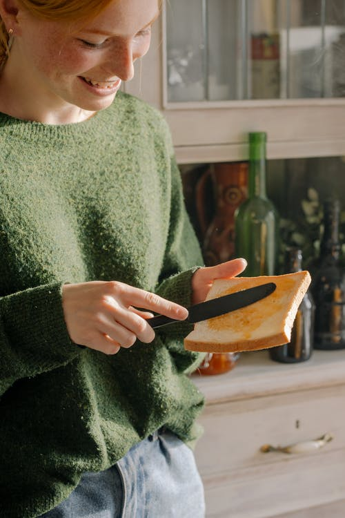 Woman in Green Sweater Holding Brown Wooden Chopping Board