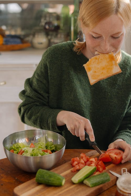 Woman in Green Sweater Holding Knife Slicing Food