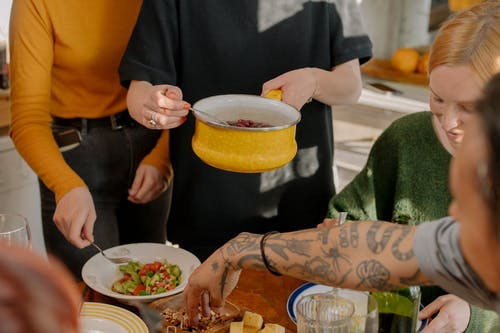 Person Holding White Ceramic Bowl With Yellow Liquid