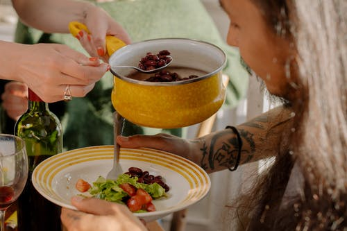 Person Holding Yellow Ceramic Bowl With Red Sauce