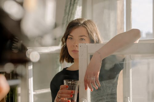 Woman in Black Shirt Holding Clear Drinking Glass