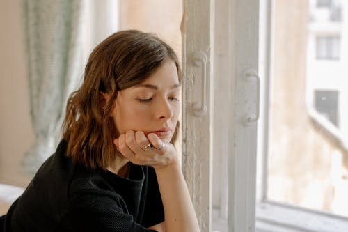 Woman in Black Shirt Leaning on White Wooden Window
