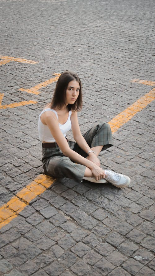 Woman in White Tank Top and Blue Denim Jeans Sitting on Gray Brick Floor