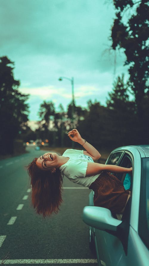 Side view of cheerful red haired female in casual clothes climbing out of automobile window and looking at camera