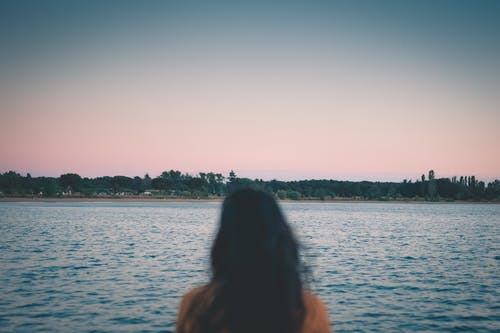 Back view of unrecognizable female standing on coast of rippling lake under colorful sundown sky