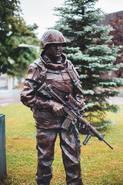 Bronze sculpture of soldier in uniform and helmet with shotgun on grass lawn in city
