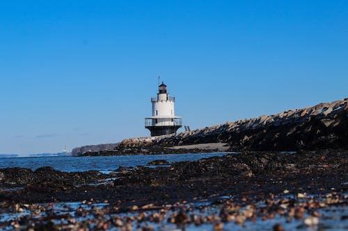 White Lighthouse on Rocky Hill Under Blue Sky