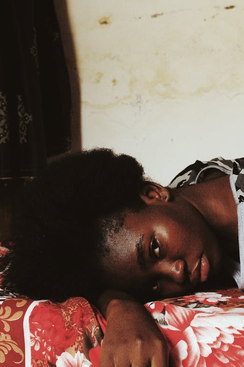 Woman in White and Black Shirt Lying on Bed