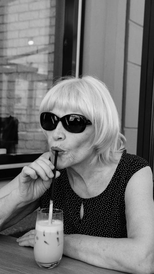 Grayscale Photo of an Elderly Woman Drinking