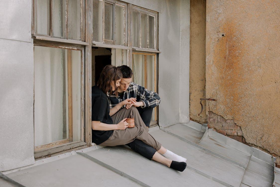Man and Woman Sitting on Window