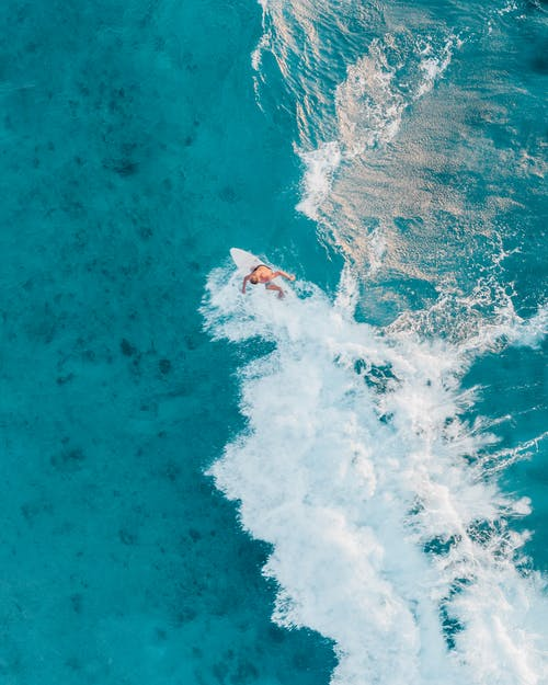 A Person Surfing on the Blue Sea