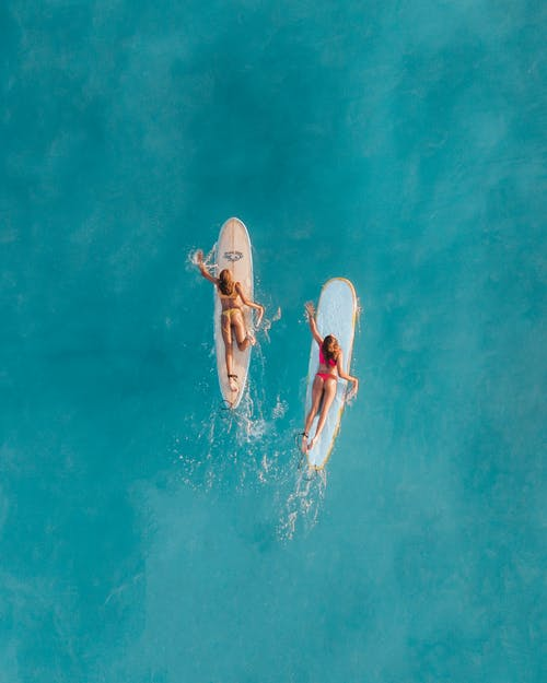 2 Women in White and Red Bikini Lying on White Surfboard on Water
