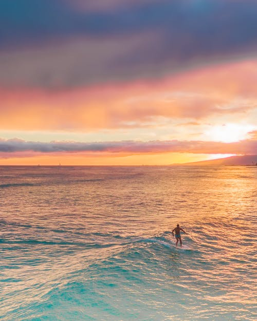 Person Surfing on Sea during Sunset