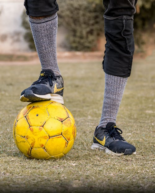 Unrecognizable crop sportsman wearing sportive socks and sneakers standing with one leg on soccer ball on grass field