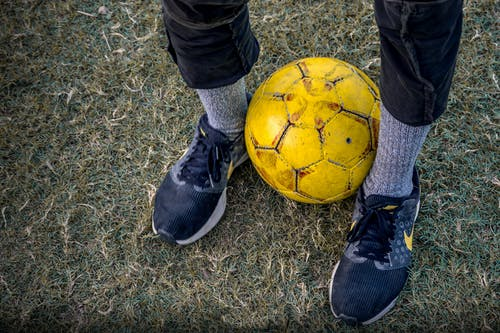 Faceless person standing with soccer ball between legs on grass