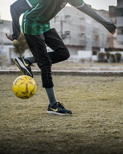 Crop sportsman kicking soccer ball on grass field in city