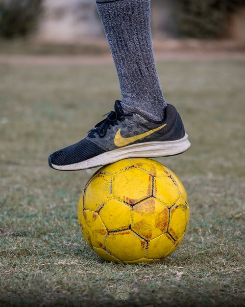 Anonymous crop person wearing gray sock and dark sneaker stepping on yellow old soccer ball on grass lawn