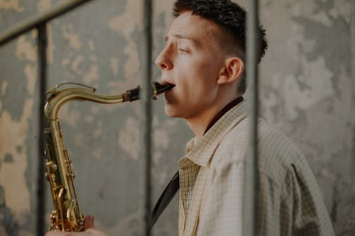 Man in White and Black Plaid Shirt Playing Saxophone