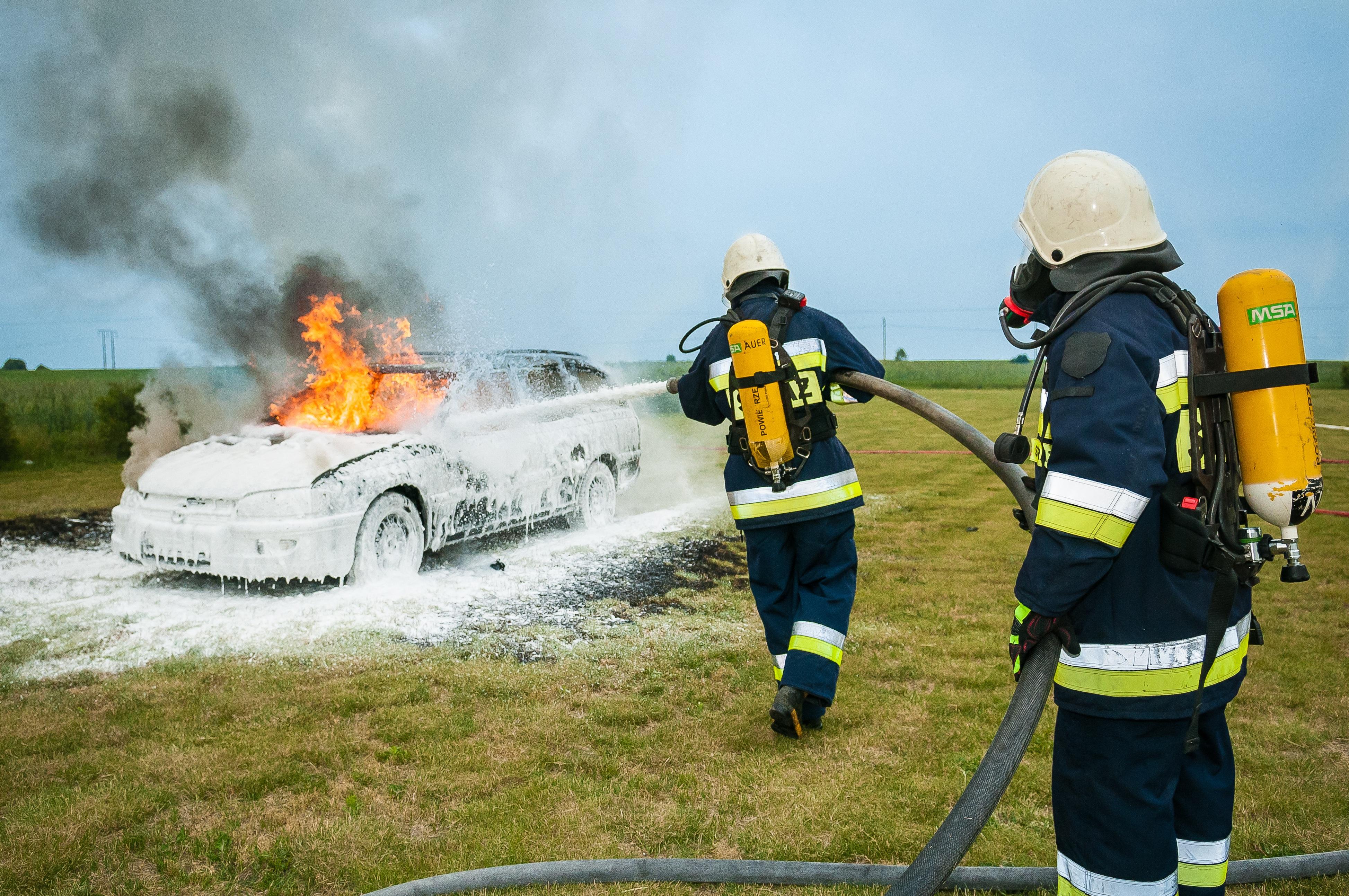 Two Firemen Spraying on Flaming Vehicle