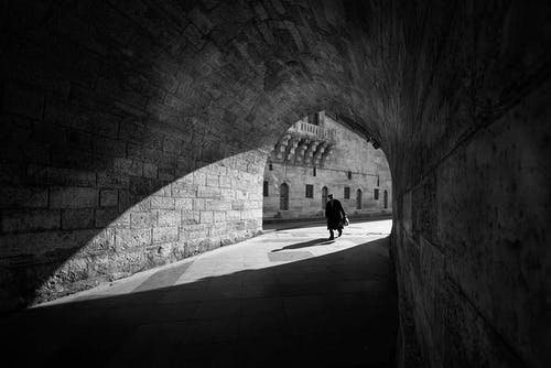 Black and white anonymous male walking along old stone tunnel near aged brick building