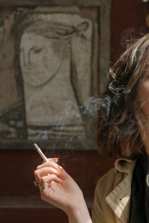 Woman in Brown Coat Smoking Cigarette