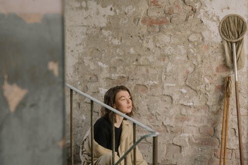 Woman in Brown Jacket Leaning on Brown Concrete Wall