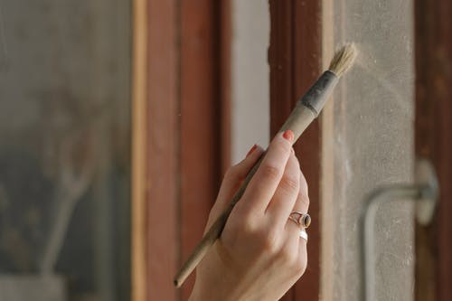 Person Holding Brown and Gray Paint Brush